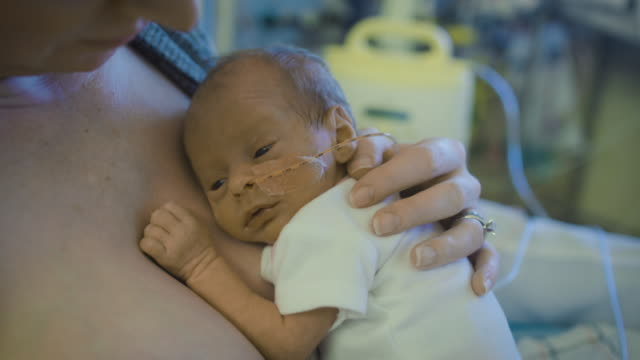 a premature newborn infant with a nasal cannula is embraced by his mother at hospital - 未熟児点の映像素材/bロール