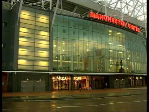 premiership; itn england: manchester: old trafford: ext manchester united megastore statue above entrance to manchester united shop - megastore stock videos & royalty-free footage