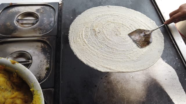 preparation and serving of dosa (crispy, savory pancakes) from south india is a popular and staple food in al of india. - savory food stock videos & royalty-free footage