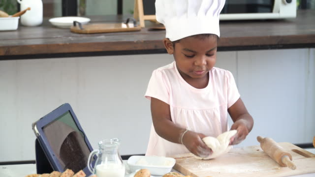 preparation bakery of a cheerful young mixed-race child between african and thai ethnic as a chef, threshing flour by herself with positive emotion and funny for baking bread for breakfast or lunch. concept of learning. - effort stock videos & royalty-free footage