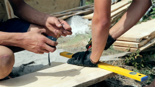 Preparation of a wooden plank for building a fence.