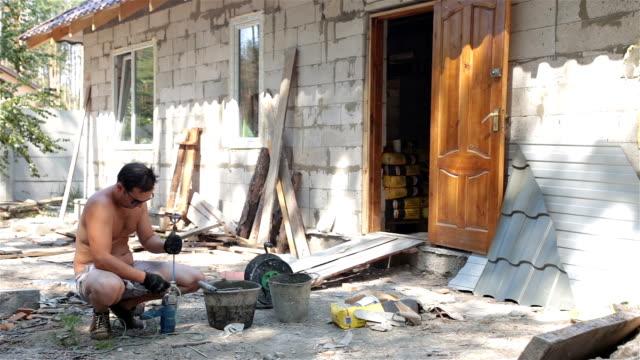 vidéos et rushes de préparation de l'outil de construction pour les travaux. - un seul homme d'âge moyen