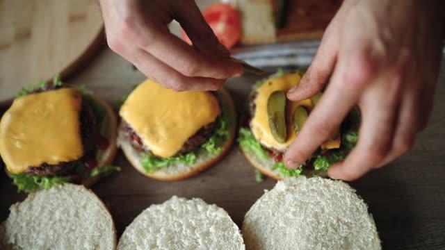 stockvideo's en b-roll-footage met bereiding van heerlijke hamburgers - burger menselijke rol