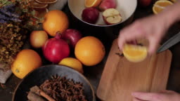 Preparation of mulled wine. Female hands cut oranges and lemons on wooden cutting board and put them in a black saucepan. Fresh lemons, oranges, pomegranate and dried herbs in background