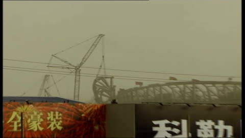 preparations for beijing olympics 2008; china: beijing: ext wet concrete being tipped from wheelbarrow at construction site ground to air cranes... - crane construction machinery stock videos & royalty-free footage