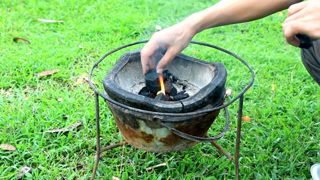 prepare coal to burning before roast pork - briquette stock videos & royalty-free footage