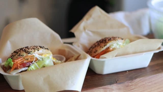 マスクとフェイスシールドを身に着けているおいしいフレッシュbltサンドイッチを準備する - 食べ物 サンドイッチ点の映像素材/bロール