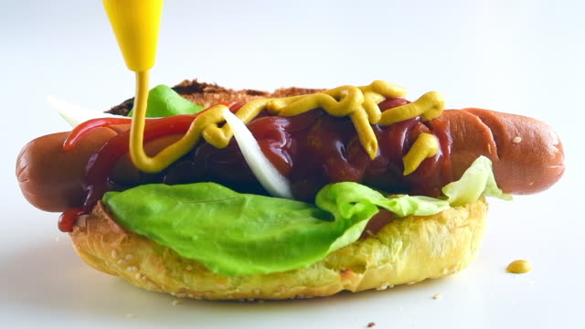 preparing a hot dog food: adding yellow mustard, slow motion - ketchup stock videos and b-roll footage