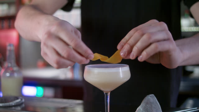 vídeos y material grabado en eventos de stock de preparing alcoholic cocktail drink in a stylish bar while night by professional bartender - seasoning / decorating. - puro