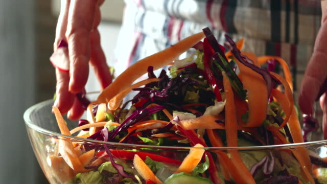 preparing and mixing fresh root vegetable salad - cucina vegetariana video stock e b–roll