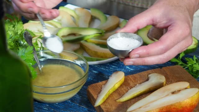 preparing avocado and pear salad - adding salt stock videos and b-roll footage