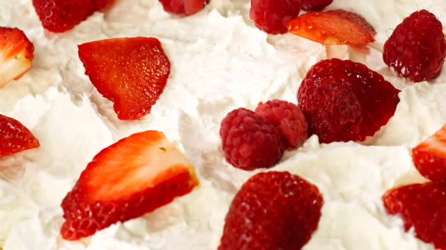 preparing berry pavlova cake with strawberries and raspberries - whipped cream stock videos & royalty-free footage