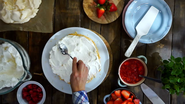 preparing berry pavlova cake with strawberries and raspberries - whipped food stock videos and b-roll footage
