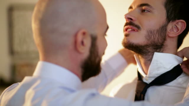 vídeos de stock, filmes e b-roll de preparing boyfriend for gay wedding - shirt and tie