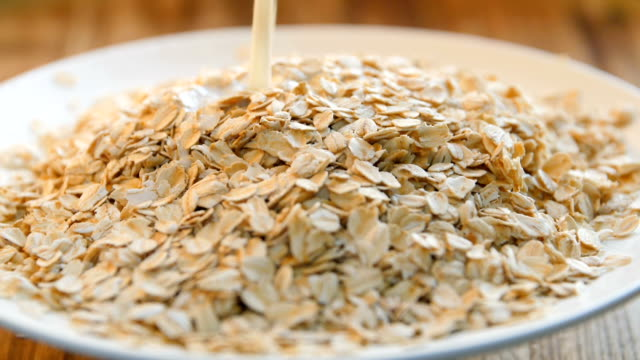 preparing breakfast,mixing oats with milk - bowl stock videos & royalty-free footage