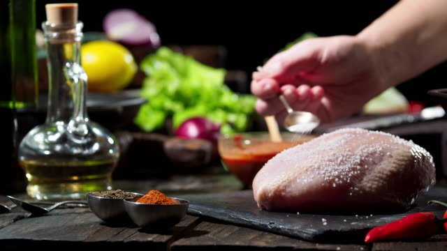 preparing chicken breast with olives - adding salt stock videos and b-roll footage