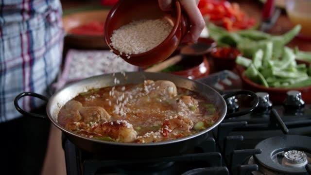 vídeos y material grabado en eventos de stock de preparación de paella de pollo con judías verdes, guisantes y pimentón - muslo de pollo carne