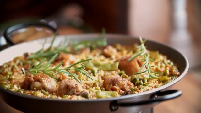 vídeos de stock e filmes b-roll de preparing chicken paella with green beans, peas and paprika - cultura espanhola