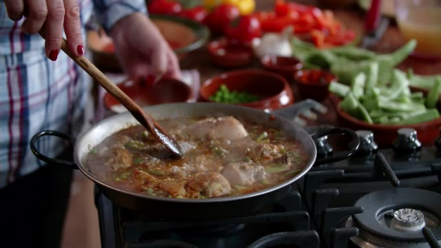 preparing chicken paella with green beans, peas and paprika - cucina mediterranea video stock e b–roll