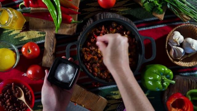 preparing chili sin carne - adding salt stock videos & royalty-free footage