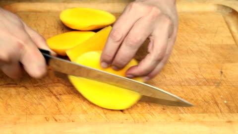 preparing, cutting mango with kitchen knife (4 of 5) (video) - mango fruit stock videos & royalty-free footage
