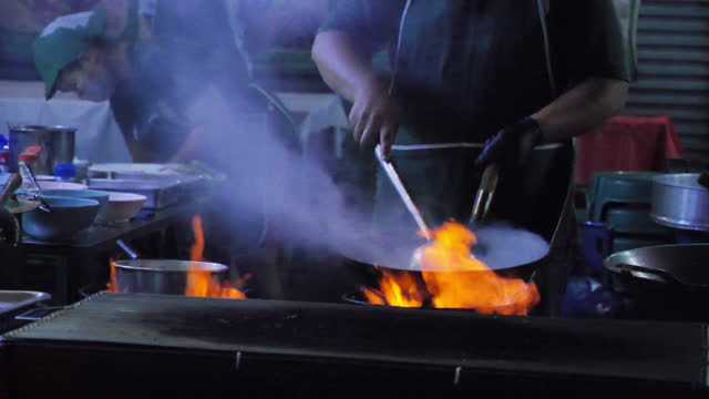 preparing food with stir fry on street. street food at yaowaraj road in bangkok's chinatown, thailand. slow motion - market trader stock videos & royalty-free footage