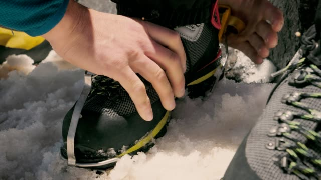 preparing for climbing on snow. fitting crampons to boots - climbing rope stock videos & royalty-free footage
