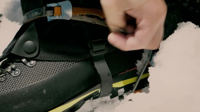 vídeos de stock e filmes b-roll de preparing for climbing on snow. fitting crampons to boots - corda de trepar