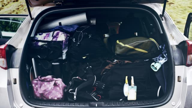 vídeos de stock e filmes b-roll de preparing for journey. fully packed car trunk - cheio