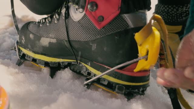 vorbereitung auf den schneefall. krampfer zu stiefeln - vorbereitung stock-videos und b-roll-filmmaterial