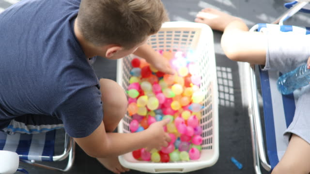 vídeos de stock e filmes b-roll de preparing for water balloon battle - bomba de água equipamento