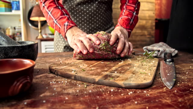 preparing fresh roast beef with herbs and spices - roast beef stock videos & royalty-free footage