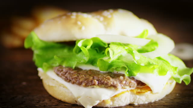 SLO MO DS Preparing hamburger with cheese, lettuce and onion