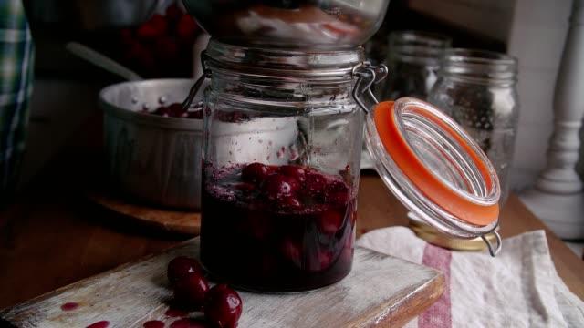 stockvideo's en b-roll-footage met voorbereiding van zelfgemaakte gekookte kersen en canning in potten - glazen pot