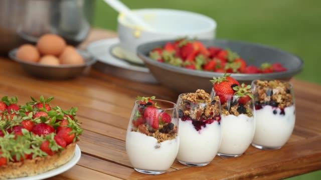 preparing homemade granola with yogurt and custard cream cake - カスタードクリーム点の映像素材/bロール