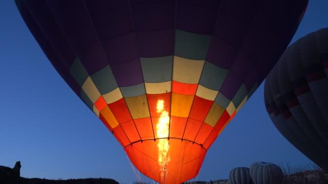 vídeos de stock e filmes b-roll de preparing hot air balloons to fly in cappadocia - balão de ar quente