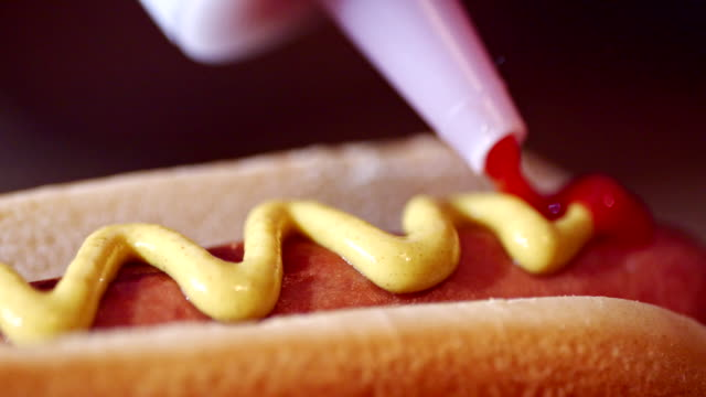 preparing hot dog with mustard and ketchup - ketchup stock videos and b-roll footage