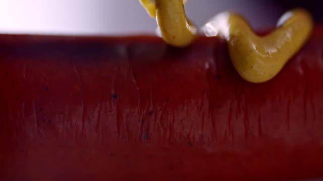 vídeos de stock e filmes b-roll de preparing hot dog with mustard and ketchup - hot dog