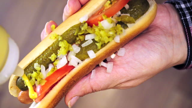 preparing hot dog with mustard, ketchup and pickles - mustard stock videos & royalty-free footage