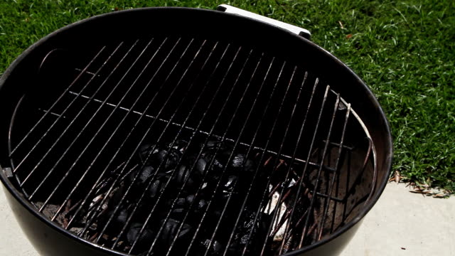 preparing & igniting a charcoal grill - briquette stock videos & royalty-free footage