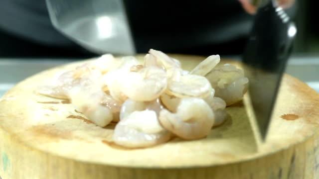 stockvideo's en b-roll-footage met bereiden ingrediënt voedsel, zet de garnalen op de houten plank en het snijden van de garnalen in kleine stukjes zal het gemakkelijker maken om te hakken. - steurgarnaal