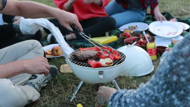 preparing meet and vegetables on a barbecue grill - fleischzange stock-videos und b-roll-filmmaterial