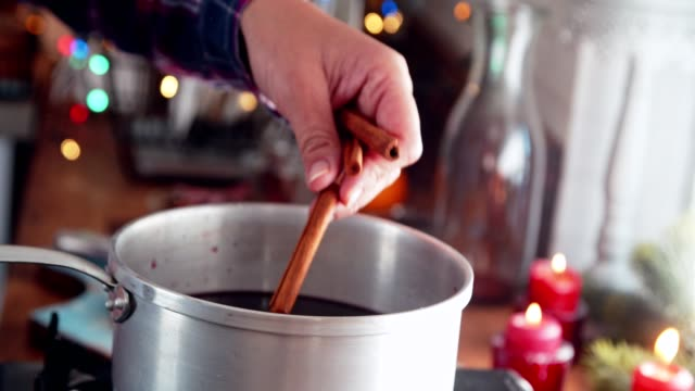 preparing mulled wine with orange, cinnamon, star anise and spices for christmas - cinnamon stock videos & royalty-free footage
