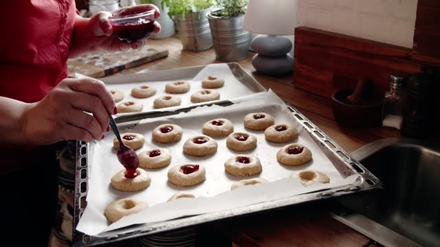 preparing peanut butter cookies with marmalade in domestic kitchen - baking stock videos & royalty-free footage