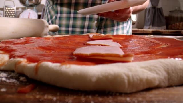 vidéos et rushes de préparation de pizza avec jambon prosciutto et basilic frais dans la cuisine domestique - quartier