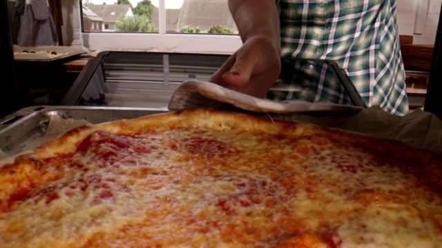 vídeos de stock e filmes b-roll de preparing pizza with prosciutto ham and fresh basil in domestic kitchen - domestic kitchen