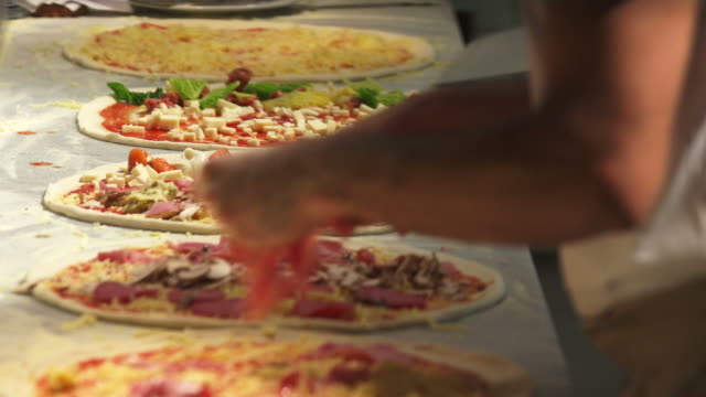 hd bereitet pizza in einer pizzeria - italian culture stock-videos und b-roll-filmmaterial