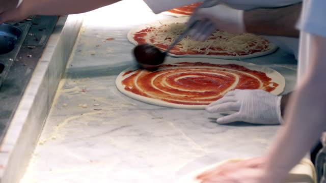 vídeos de stock e filmes b-roll de preparing pizzas in a restaurant - fazer