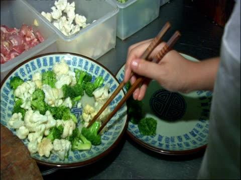 Preparing presentation of stir-fried vegetables, Beijing, China