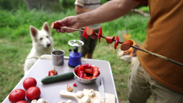 Preparing sausage and vegetables on skewer